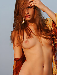 Red haired model naked on a rocky mountain.