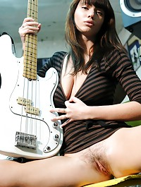 Ultra seductive brunette baring her large breasts and untrimmed bush with an electric guitar.