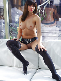 Wide and open Taira in faux snakeskin belt and thigh-high stockings by the couch.