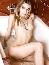 Izolda poses in the bathroom with an inviting look on her face before bathing her gorgeous body in the bathtub.