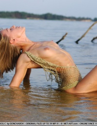Cute girl on the beach sticks her butt in the air