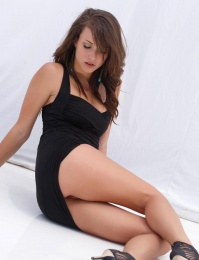 erotic allure as she flirts and strips her sexy black dress in front of the camera