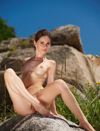 Fresh skinny girl naked on the rocks by the beach