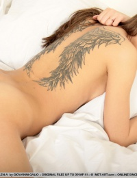 hot girl nude on bed with a wicked tattoo on her back