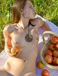 laid-back allure as she sprawls confidently with a bunch of ripe apples