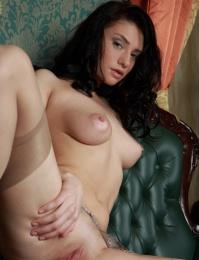 Seductively elegant model with graceful yet erotic poses on the sofa