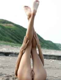 shapely limbs as she sprawl on the sandy shore