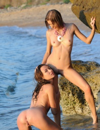 Two hot chicks on the beach playing with each other